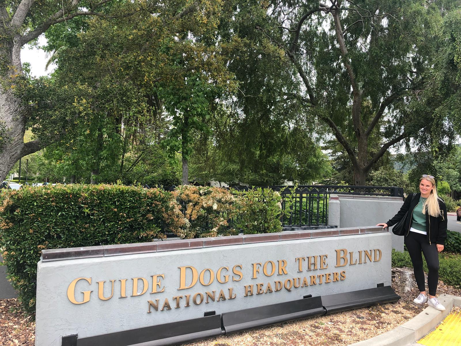 Teresa Seitle steht rechts neben dem Schild: Guide Dogs for the blind