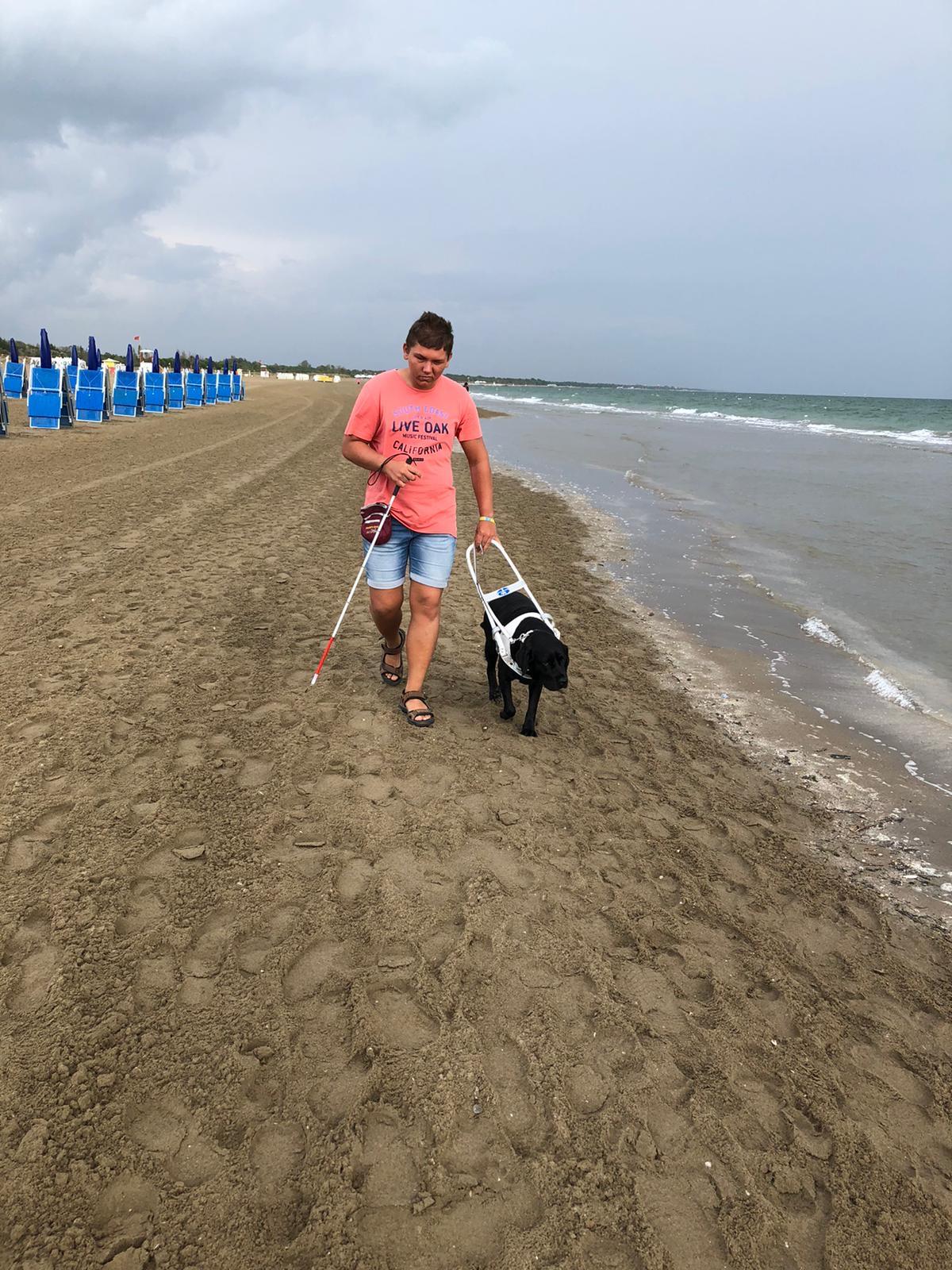 Dustin läuft mit Führhund Una am Strand entlang